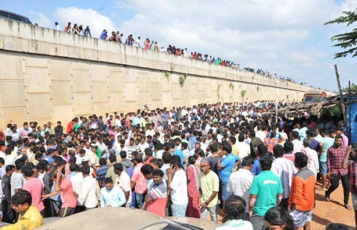 A large number of people gather on the service road in Tumakuru the former Mayor Ravi Kumar was hacked to death on Sunday. (DH Photo)