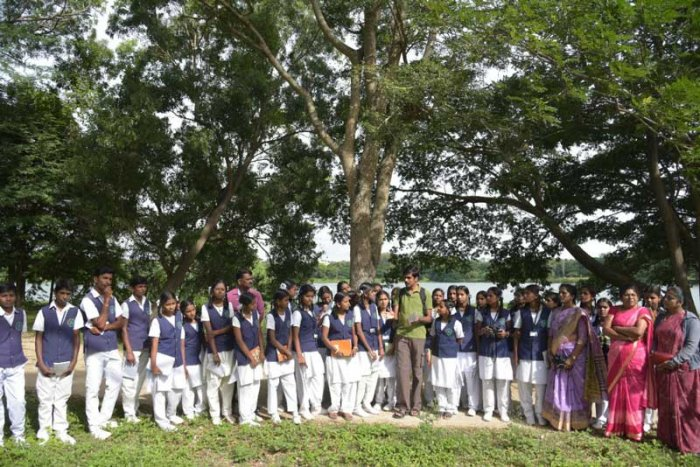 Deputy Commissioner Abhiram G Sankar interacts with school students, during a nature watch programme, organised by Wild Mysuru. (DH/PV Photo)