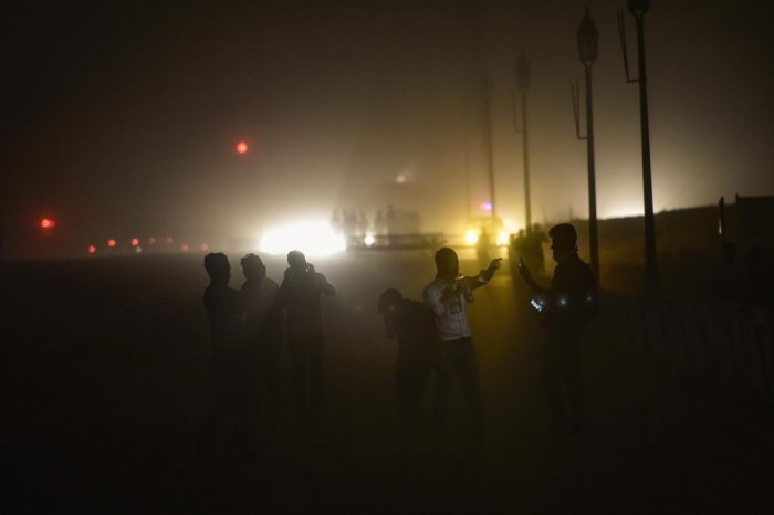 People cross a road as it gets dark during a dust storm before rains and thunderstorm, in New Delhi on Saturday. PTI