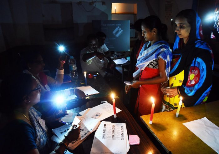 Election officials had to use candles to help voters as there was a power shutdown due to rain at a booth at Hubballi on Saturday. dh photo/Tajuddin Azad