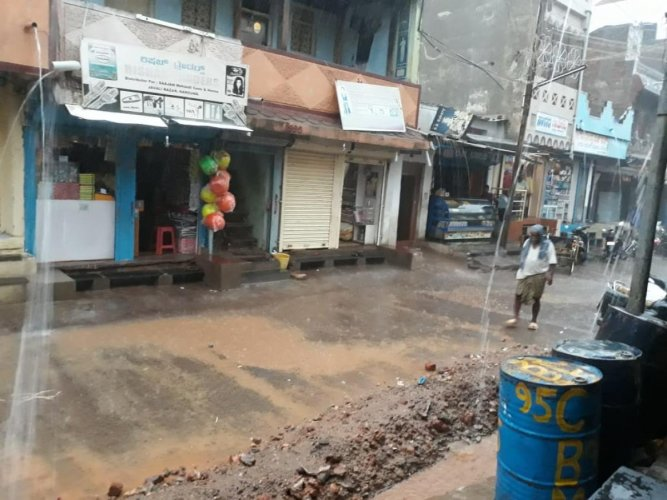 Heavy rain lashes Nargund town in Gadag taluk on Monday. (Right) The KSRTC bus stand in Chamarajanagar was flooded due to downpour on Monday. DH Photos
