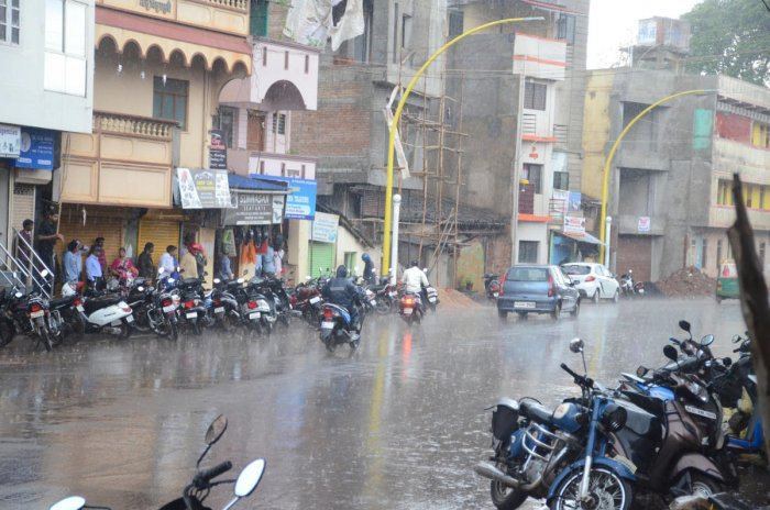 People taking shelter before shops during the downpour at Patil Galli in Belagavi on Tuesday.