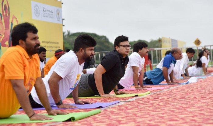 MLA L Nagendra, MP Pratap Simha, scion of Mysuru's erstwhile royal family, Yaduveer Krishnadatta Chamaraja Wadiyar, MLA S A Ramdas, Minister Sa Ra Mahesh and others perform Yoga, on the occasion of International Yoga Day, at Mysore Race Course grounds on