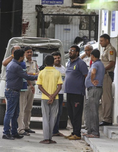 A family member of the 75-year old woman who was among the 11 members of a family found dead at a house in Burari, speaks with police personnel outside Maulana Azad Hospital Mortuary, in New Delhi on Monday. PTI