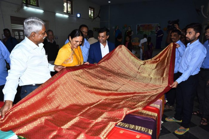 Dimhans administrative officer Sharada Kolakar and others look at a saree at the inauguration of the four-day Mysore Silk exhibition-cum-sale at Bhagini Mandal at J C Nagar in Hubballi on Tuesday.