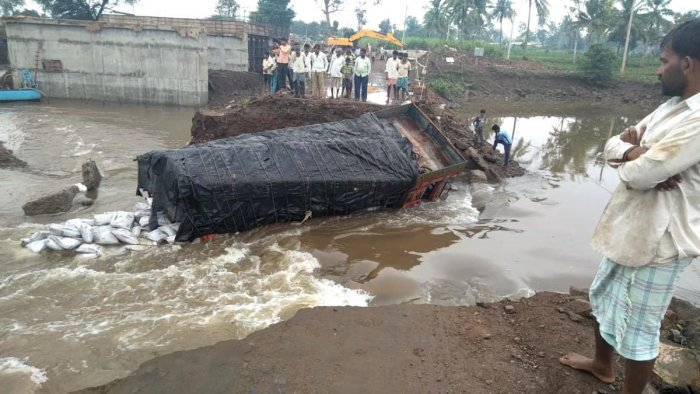 A cement-laden truck got washed away when the bridge it was on, collapsed in Mudalgi taluk, Belagavi district on Tuesday. DH photo.