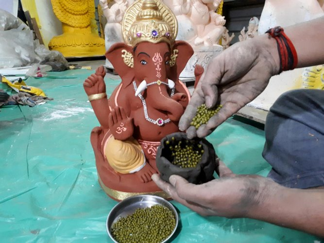 Greengram seeds are put inside the Ganesh idols before handing them over to devotees. (DH Photo)