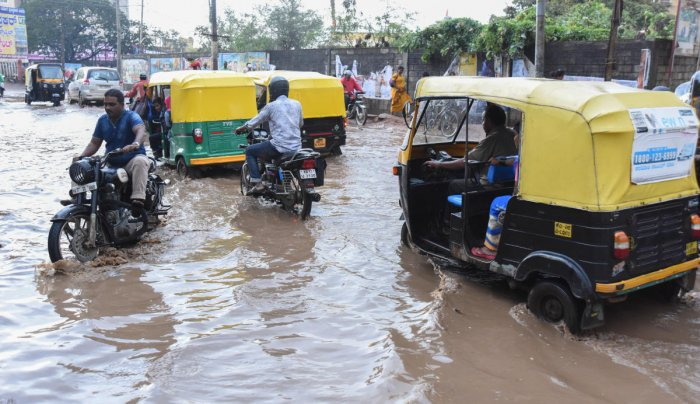Vehicles wade through the waterlogged Ashoka Road in Davangere on Friday. The city has been receiving good spells of rain for the past two days. DH PHOTO