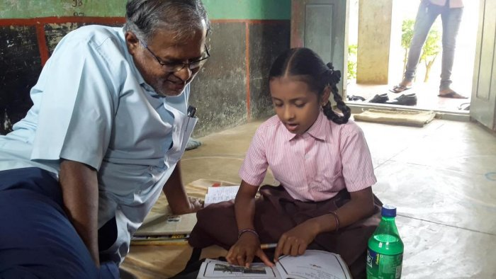 MLA Suresh Kumar listens to Nanditha as she reads out a poem for him at the Obenahalli government school, Srinivaspur taluk in Kolar district.