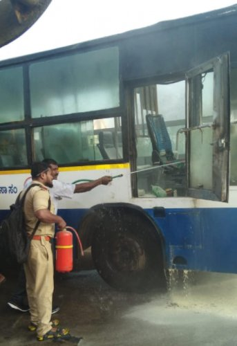 Fire personnal put off the fire and smoke from inside the BMTC bus which got fire due to short circuit near Bengaluru International Exhibition Center at Madapura in Bengaluru on Monday.