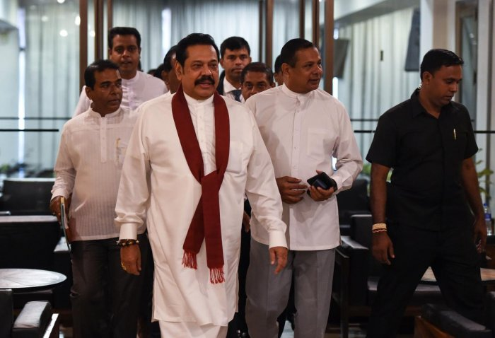 Sri Lanka's former president and currently appointed prime minister Mahinda Rajapakse (C) arrives at the parliament in Colombo on November 29, 2018. AFP
