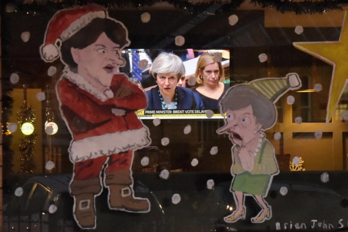 People in a bar watch Britain's Prime Minister Theresa May during a debate in the house of Commons on television as a window is illustrated with DUP leader Arlene Foster as Santa Claus and Theresa May as a Christmas Elf in Lisburn, Northern Ireland Decemb