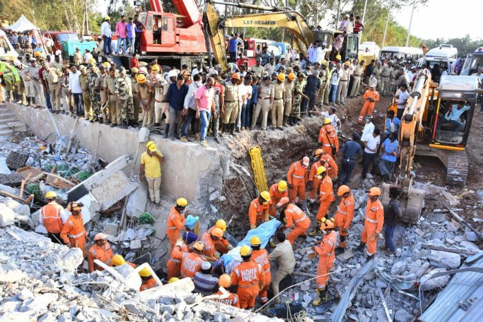 Personnel of the National Disaster Relief Force retrieve the body of a victim from under the debris of the collapsed building in Dharwad on Wednesday. dh photo/Tajuddin Azad