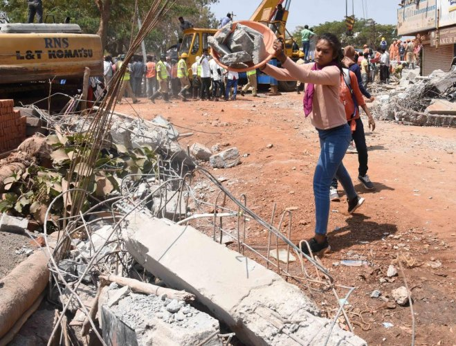 Students clear debris at the building collapse site.