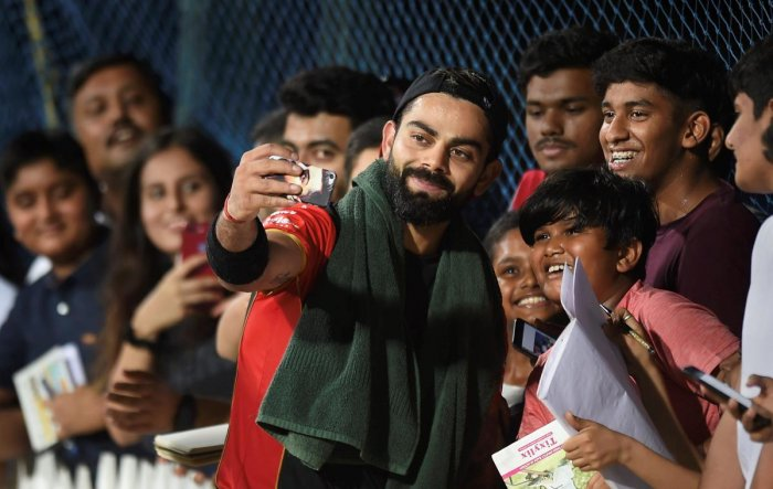 Royal Challengers Bangalore skipper Virat Kohli takes a selfie with fans at the M A Chidambaram Stadium ahead of the IPL. PTI
