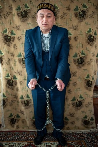 """Omir Bekali, a Kazakh who was imprisoned and sent to a """"reeducation camp"""" in China, shows how he was chained during his detention during an interview in Istanbul. AFP."""