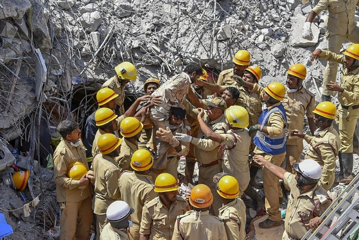 NDRF team members recover a survivor during a rescue operations, four days after an under construction building collapsed at Dharwad in North Karnataka, Friday, March 22, 2019. (PTI Photo)