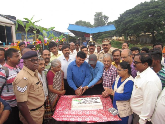 Passengers and officials cut a cake to mark the fifth anniversary of Tumakuru-Bengaluru Fast Passenger at the Tumakuru railway station on Friday.