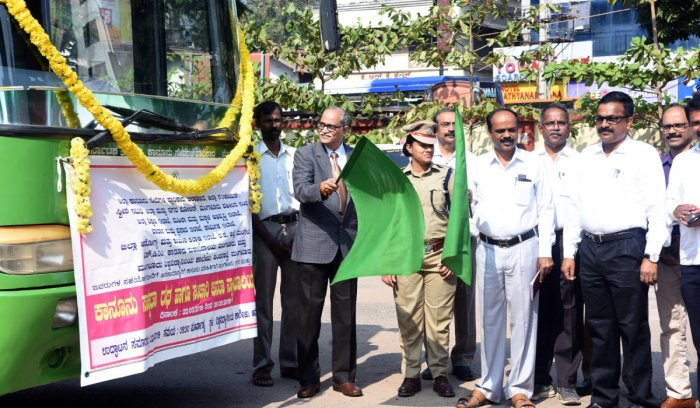 Principal District and Sessions Judge Kadluru Satyanarayanacharya flags off the Legal Awareness Chariot and the Mobile Janata Court on the premises of the University College in Mangaluru on Friday.