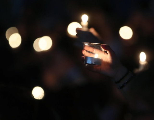 (FILES) In this file photo taken on February 15, 2018, students and family members hold candles during a vigil for victims of the mass shooting at Marjory Stoneman Douglas High School Feburuay 14, 2018, at Pine Trail Park, in Parkland, Florida. - A teenag