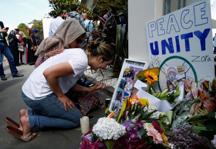 A woman cries next to a tribute to victim Hussein Al-Umari outside Al-Noor mosque after it was reopened in Christchurch, New Zealand, March 23, 2019. REUTERS/Edgar Su