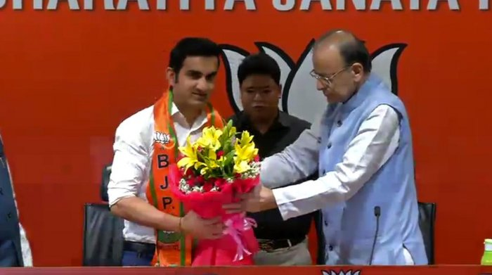 Union minister Arun Jaitley hands over a bouquet to Gautam Gambhir at BJP headquarters in New Delhi on Friday. (Twitter/@BJP4India)