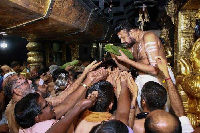 Sabarimala head priest Kandararu Rajeevarau gives 'prasad' to devotee, at Sabarimala temple in Sabarimala. PTI Photo