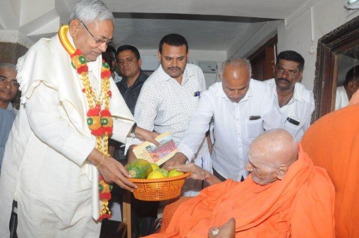 Bihar Chief Minister Nitish Kumar seeks blessings of Siddaganga mutt seer Shivakumara Swamiji in Tumakuru on Sunday.