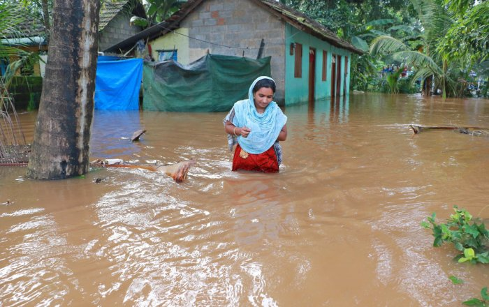 A woman wades through flood water in Eloor in Ernakulam district. DH Photo