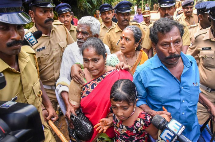 Police escort Madhavi and her family members after she was heckled by protesters while seeking entry to the Ayyappa Temple on Wednesday. PTI