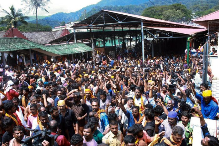 Devotees protest as several female devotees arrive to offer prayers, at Sabarimala temple in the light of the recent verdict by the Supreme Court allowing entry to women of all ages, in the hill shrine, on Sunday. PTI