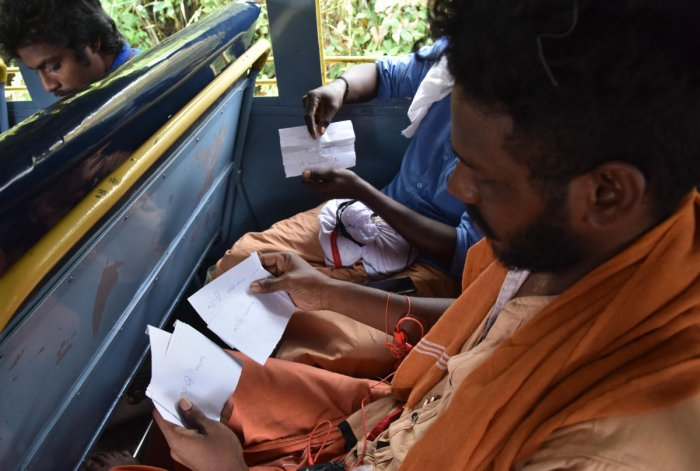Devotees display the paper strips with the words 'Swamy Sharnam', which they plan to drop in offering box instead of money as part of the protest in the Sabarimala Ayyappa temple. DH photo/ B H Shivakumar