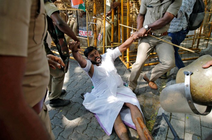 Police officers detain a member of the youth wing of Congress party during a demonstration outside the police commissioner's office demanding to lodge a case against a driver of the cavalcade of the state's chief minister after it hit one of their members