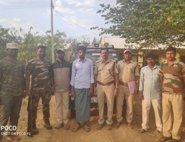 Forest department personnel with the accused, Arun Kumar, at Bandipur, on Thursday.