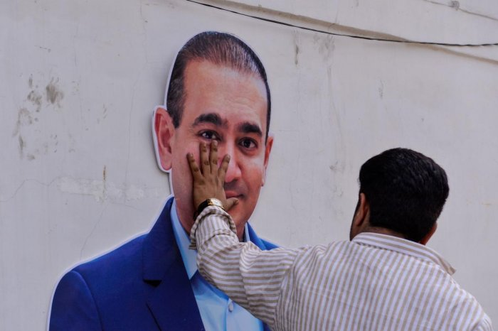 A man keeps his hand on a cut-out of billionaire jeweller and loan defaulter Nirav Modi in New Delhi on February 16, 2018. AFP