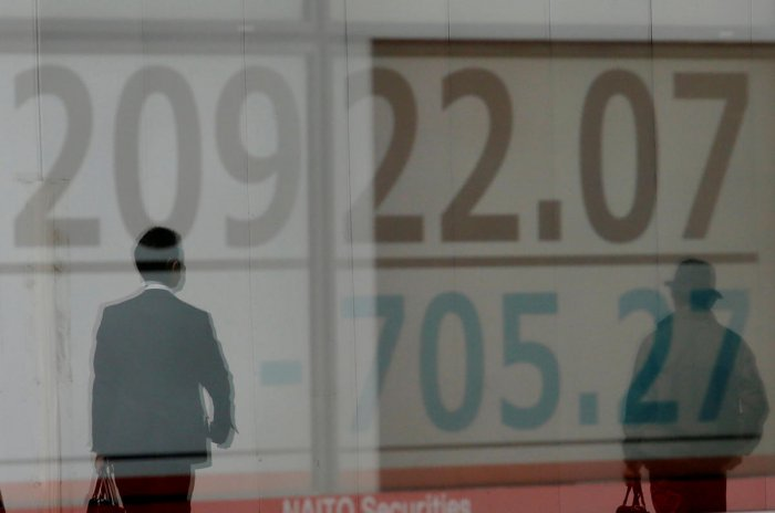 Men are reflected on an electronic board showing the Nikkei stock index outside a brokerage in Tokyo. Reuters