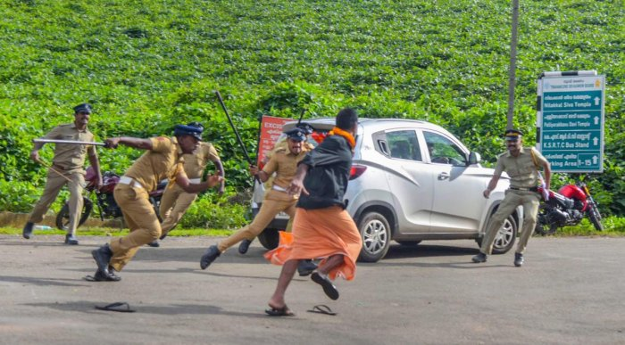 Police lathi-charge one of the protesters after they opposed the entry of girls and women of menstrual age into the hill shrine of Lord Ayyappa Temple in Sabarimala, Kerala, Wednesday, Oct 17, 2018. Tension was witnessed outside the temple on its opening day. PTI