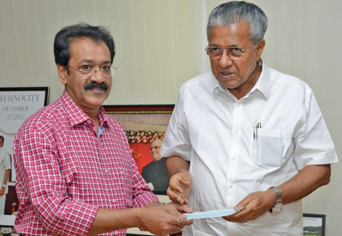 Kerala Chief Minister Pinarayi Vijayan receives a cheque for Rs 1.36 crore towards Chief Minister's Distress Relief Fund from B S Arun, Deputy Editor, Deccan Herald, in Thiruvananthapuram on Tuesday. The Kerala-Karnataka Relief Fund was set up by The Printers (Mysore) Pvt Ltd, publishers of Deccan Herald and Prajavani.