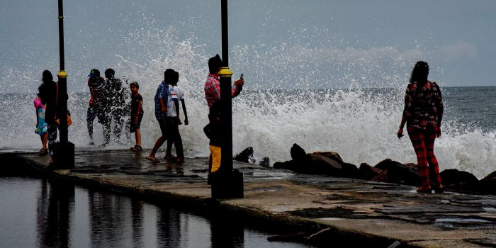 People react as a big wave hits the seawall during sunset, in Kochi, Kerala, on Wednesday. According to the Meteorological Department, the southwest monsoon hit Kerala, three days before its scheduled arrival. PTI