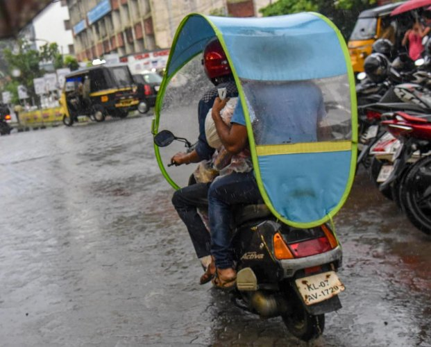 People ride a scooter with a cover as it rains in Kochi. The southwest monsoon arrived in Kerala on Tuesday, three days ahead of schedule. PTI