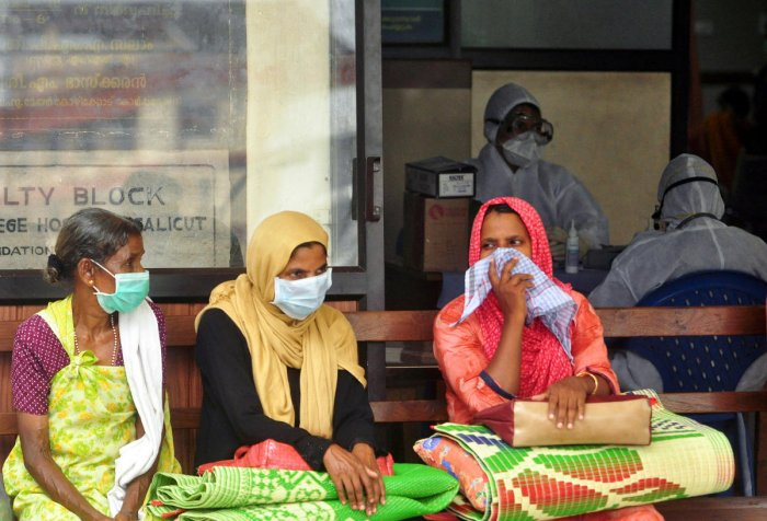 People wear masks as they wait outside a casualty ward at a hospital in Kozhikode. Reuters Photo