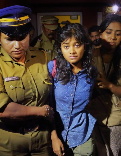 Cops move Hanan Hamid away from a massive crowd gathered around her, in Kochi. PTI