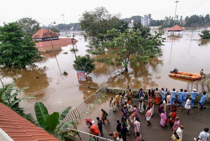 Devotees perform 'Bali tharpan' on the occasion of 'Karkitaka Vavu' near Aluva Mahadeva temple on the banks of the flooded Periyar in Kochi on Saturday. PTI