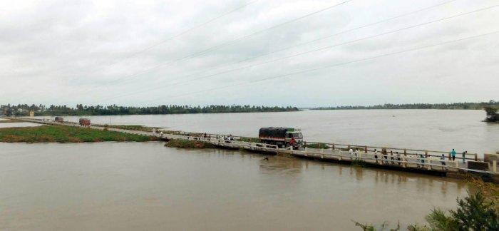 Trucks move on a bridge across a swollen Tungabhadra river near Kampli in Ballari district on Sunday.