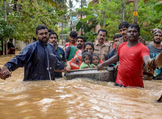 Rescuers evacuate people from a flood-hit locality, in Thiruvananthapuram on Wednesday. PTI Photo
