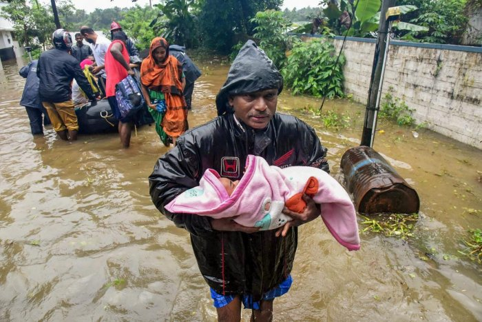 A rescuer carries an infant as people are evacuated from a flood-hit locality in Kochi on Wednesday.