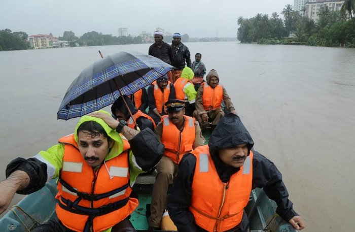 Indian fire and rescue personnel evacuate local residents in a boat following monsoon rains at Aluva, Kerala, on Thursday. AFP
