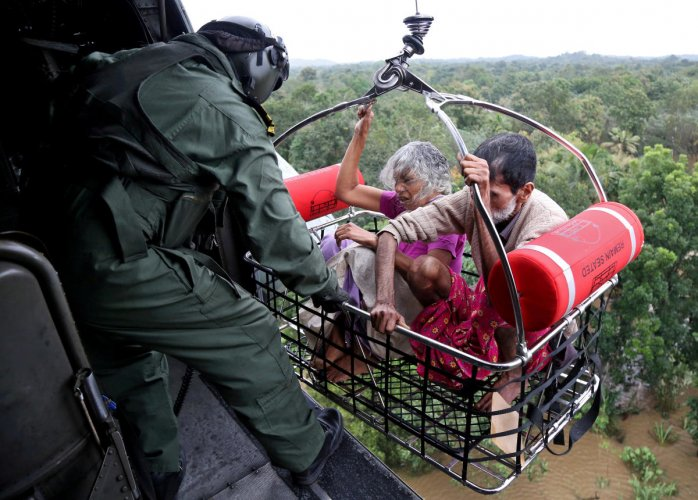 People are airlifted by the Indian Navy soldiers during a rescue operation at a flooded area in Kerala. REUTERS