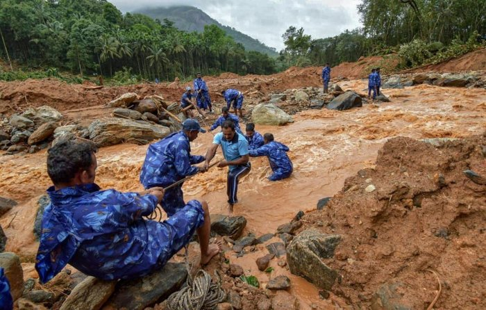 Rescue workers search for the bodies of missing persons after a landslide, triggered by heavy rains and floods, at Nenmara in Palakkad on Friday. PTI