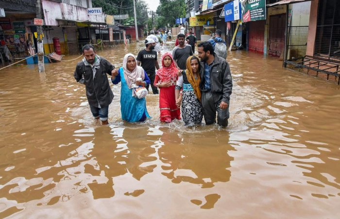People wade across a waterlogged street after being rescued from flood-affected regions following heavy monsoon rainfall, in Kochi on Saturday. PTI
